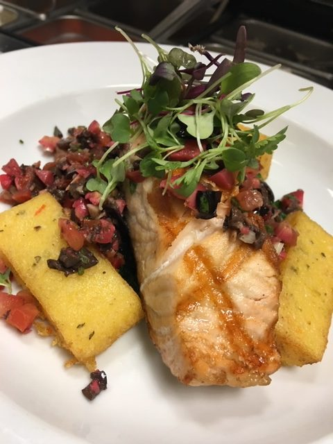 Grilled salmon with tomato relish caper and olive oil served with crispy polenta.