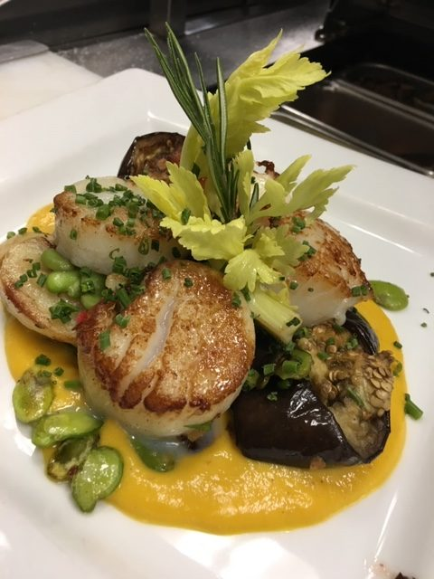 Pan seared sea scallops, roasted egg plant, fava beans with sweet yellow pepper sauce.
